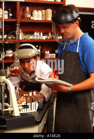 High school two boys wearing protective gear in science class - Stock Photo