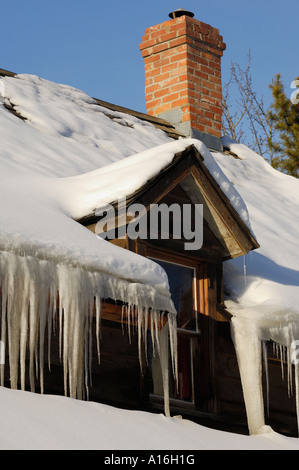 Large icicles hanging from roof eaves - Stock Photo