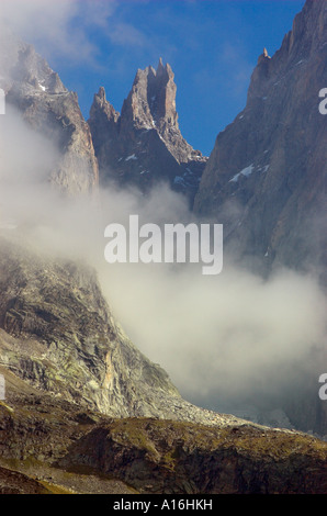 Cloud clearing from the twin towers of Les Dames Anglaises on the Peuteret Arete in the Italian Alps - Stock Photo
