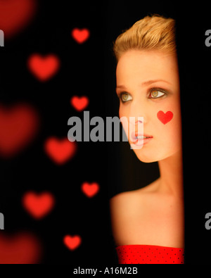 Portrait of young woman 18, 19, 20-24, 24-29, 30-34, years old with red heart painted on her cheek - Stock Photo