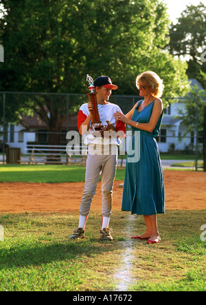 Mother congratulating her son after baseball game - Stock Photo