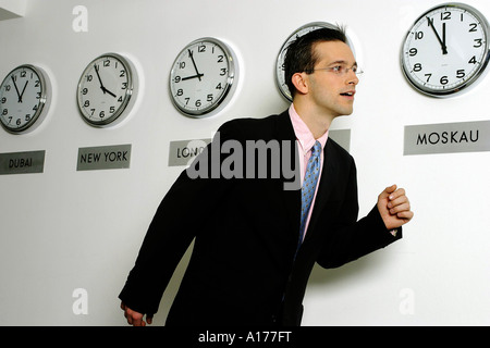 Man under stress in front of world time clocks - Stock Photo