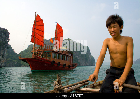 2007 Vietnamese Boy in front of Traditional Junk Sailboat with Red Sails Halong Bay Vietnam - Stock Photo