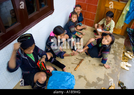 2007 Hmong Girls in Traditional Clothing Hand Sew Material and Play a Game with Sticks Sapa Vietnam - Stock Photo