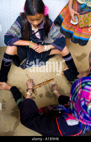 Hmong Girls In Traditional Dress Play a Game with Sticks Sapa Vietnam - Stock Photo