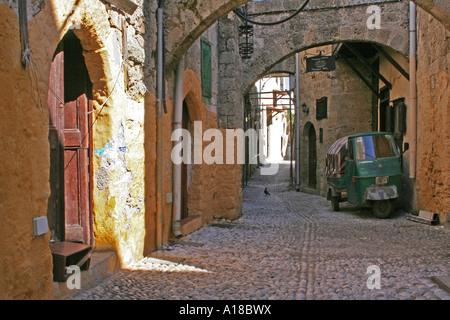Small, Greek back street with ray of sunlight casting down on house - Stock Photo