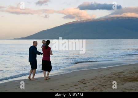 Mother, Father and Baby Walking on the Beach at Sunrise in Maui, Hawaii - Stock Photo