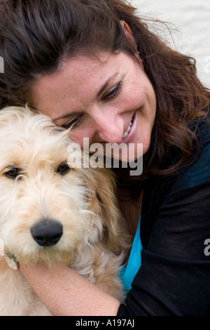 Woman age 39 enjoying her pet doodle. Poodle golden retriever crossbreed. St Paul Minnesota USA - Stock Photo