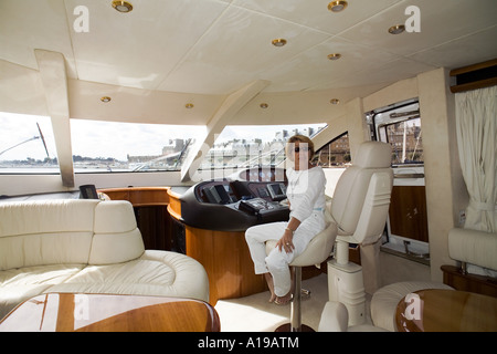 Woman sitting inside a private luxury yacht France Europe - Stock Photo