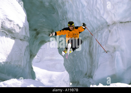 Extreme skier jumping through glacial arch on the Mer de Glace Chamonix France - Stock Photo