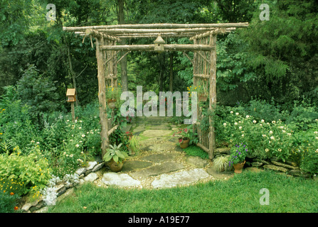 Cottage garden with flagstone path through rustic cedar arbor archway leading into shade garden and handmade birdboxes - Stock Photo