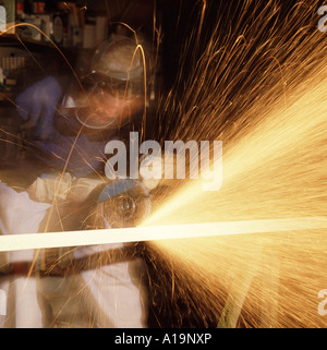 Workman in protective safety gear using a hand held disc cutting grinding machine - Stock Photo