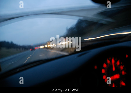 Driving on the M1 motorway in the early morning with dark blue sky and head tail lights streaming viewed through - Stock Photo