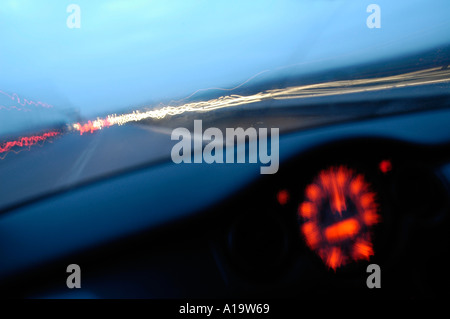 Driving in a BMW Mini on the M1 motorway in the early morning with dark blue sky and head tail lights streaming - Stock Photo