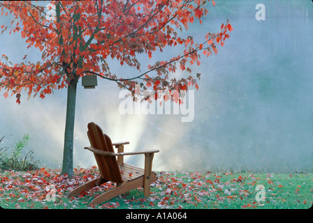 Adirondack chair sites under fall Maple tree looking out over dreamy lake as sun streaks through mist, Midwest USA - Stock Photo