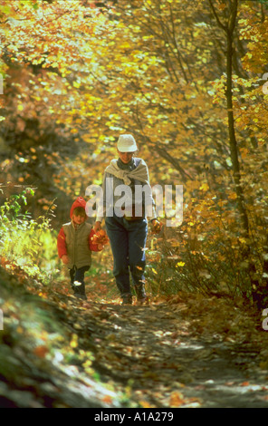 Mother and young daughter holding hands and walking together along a path in the woods during autumn - Stock Photo