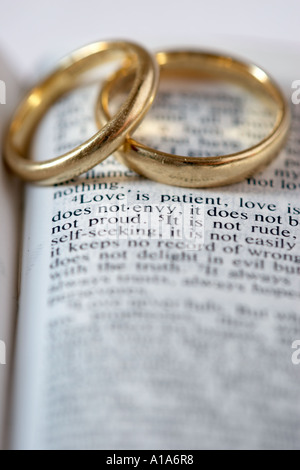 Two Gold Wedding Rings Lie On An Open Bible The Verses Are From 1 Corinthians