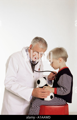 Doctor listening to boy's chest - Stock Photo
