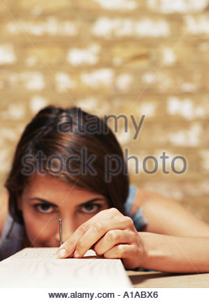 Woman holding nail on wood - Stock Photo