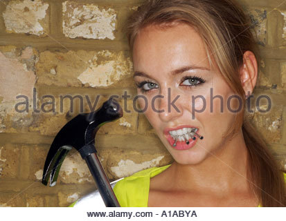 Female builder using a claw hammer - Stock Photo