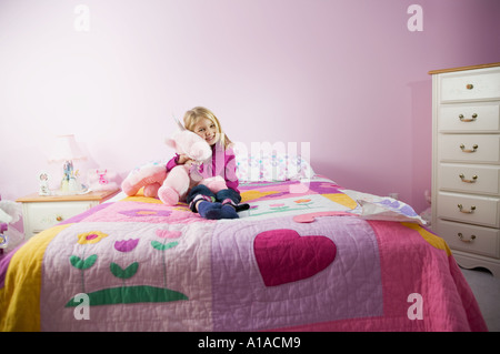 Girl hugging a toy in her room - Stock Photo