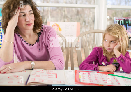 Frustrated mother helping bored daughter with homework - Stock Photo
