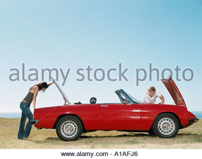 Couple having car trouble - Stock Photo