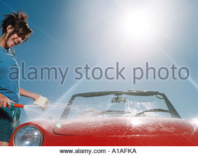 Young woman washing car - Stock Photo