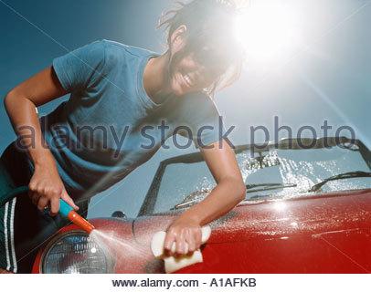Young woman washing car - Stock Photo