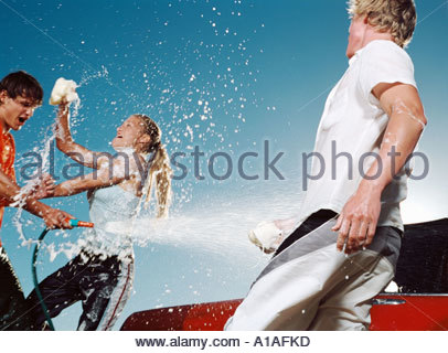 Young people washing car and having water fight - Stock Photo