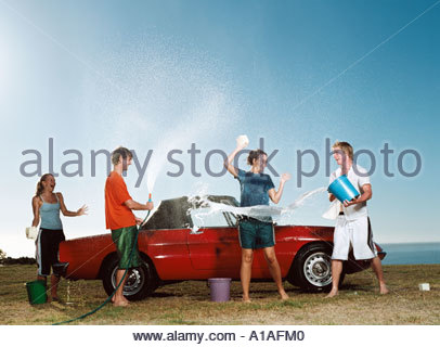 Young people having water fight and washing car - Stock Photo