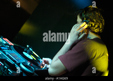 Club DJ Behind the Decks of a Nightclub Cutting in a Track on a Turntable - Stock Photo