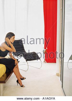 Stylish woman sitting on a bed - Stock Photo