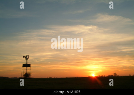 Derelict windmill in a field silhouetted by the setting sun - Stock Photo