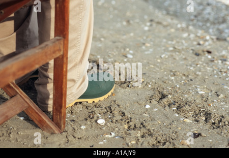 Person in rubber boots sitting in deck chair - Stock Photo