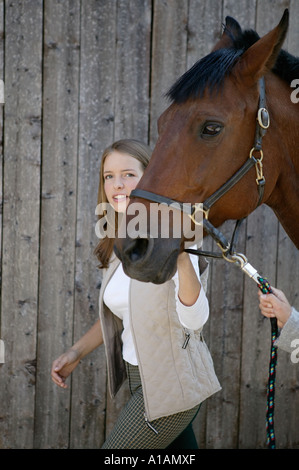 Young woman leading a horse - Stock Photo