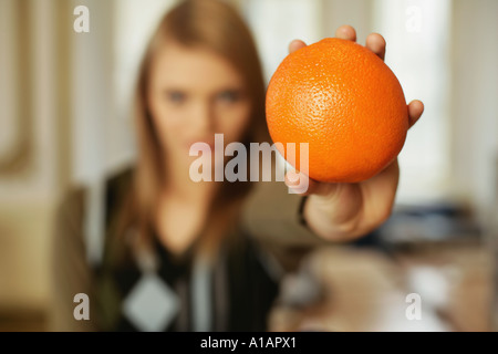 Woman holding out an orange - Stock Photo