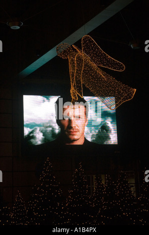 A large TV screen featuring English footballer David Beckham at a shopping mall with Christmas decorations in Prague - Stock Photo
