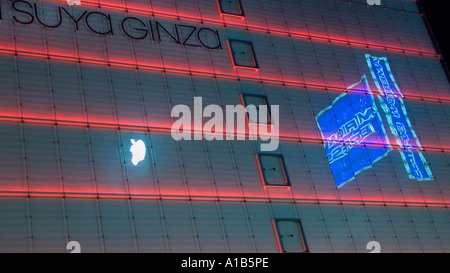 Architectural detail of the Matsuya Ginza department store with reflections of corporate logos in the glass facade - Stock Photo