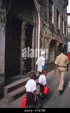 Pedestrians in the street Ornate carved doors are a commonplace sight in Stone Town Unguja Zanzibar Tanzania - Stock Photo