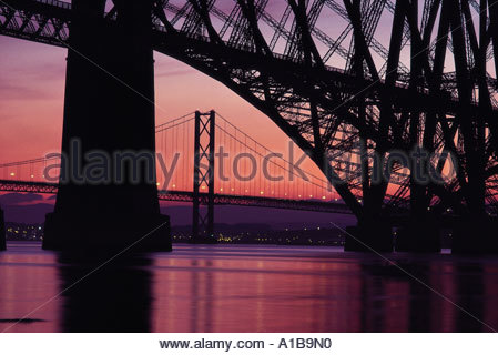 LOOKING AT SUNSET FROM THE SOUTH SHORE OF THE FIRTH OF FORTH WITH THE FORTH RAIL AND ROAD BRIDGE IN VIEW EDINBURGH - Stock Photo
