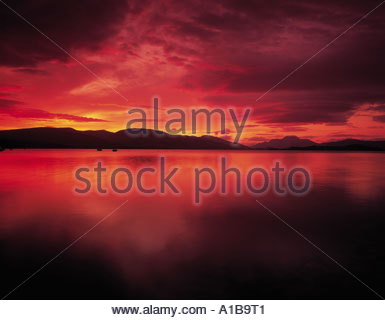LOOKING ACROSS LOCH LOMOND FROM THE SHORELINE WITH HILLS AND MOUNTAINS INCLUDING BEN LOMOND ON THE RIGHT BEYOND - Stock Photo