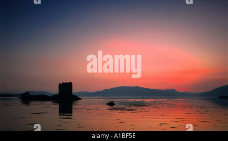 Glowing pink sunset over Castle Stalker near Oban, western Scotland, UK - Stock Photo