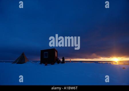On the satellite iridium phone to home from remote hunting cabin south of Igloolik or Iglulik Nunavut northern Canada - Stock Photo