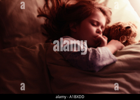 Child in bed cuddling teddy bear sucking fingers - Stock Photo