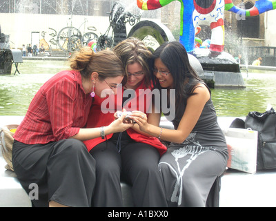 image no 3 of three female students taking digital picture in front of Tinguely fountain at Place Igor Stravinsky - Stock Photo