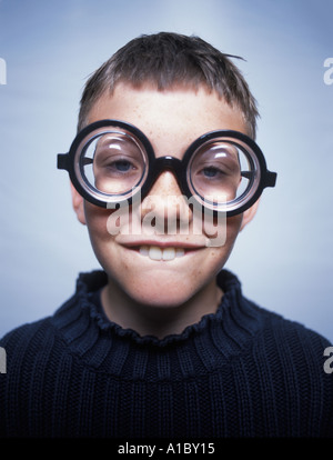 Portrait of a goofy young boy wearing thick glasses - Stock Photo