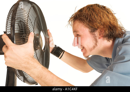 Man with blue shirt cooling down in front of a fan - Stock Photo