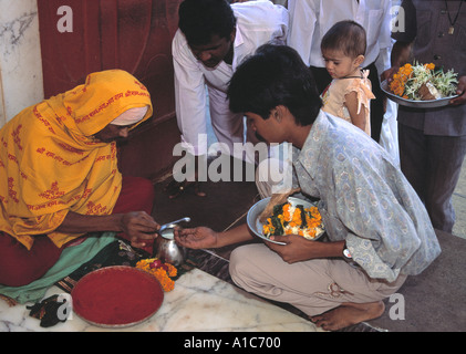Making a donation to a sadhu holy man Mahalaxmi Temple in Bombay - Stock Photo