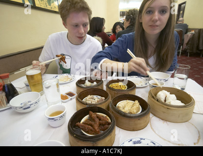 a teenage couple aged 16 on day trip to London eating Dim Sum with chopsticks at Chinese restaurant Chuen Chuen - Stock Photo